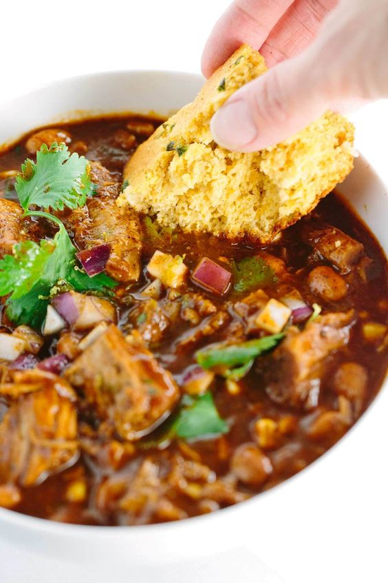Slow Cooker New Mexican Red Pork Chili - This hearty recipe is packed with rich spices, extremely tender pork, corn, and beans. A simple and easy to prepare meal that's great for a crowd!