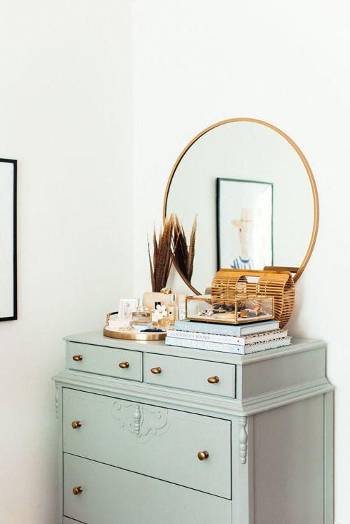 light smokey blue dresser with a round gold mirror