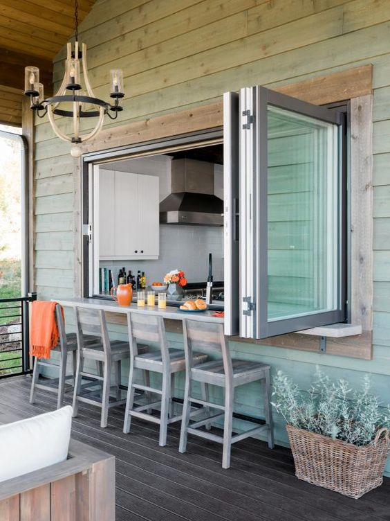 An outdoor breakfast nook! A retractable window from the kitchen opens to create a pass-through and outdoor bar. And because the bar is underneath a covered area of deck, you can use it when it's raining—or snowing. #breakfastnook #homedesign #designinspiration #kitchenideas #realtordotcom