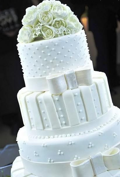 Esse bolo conseguiu reunir vários elementos (flores, poás, listras e laços) e não ficar extravagante (beirando o feio).