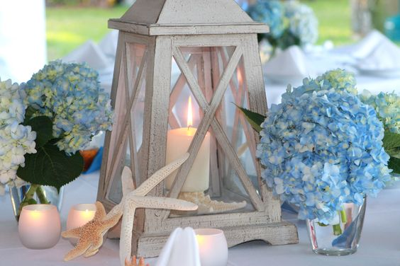 looove this lantern. looooove. lose the hydrangeas, surround the candle with sand and shells, and you have my dream centerpiece