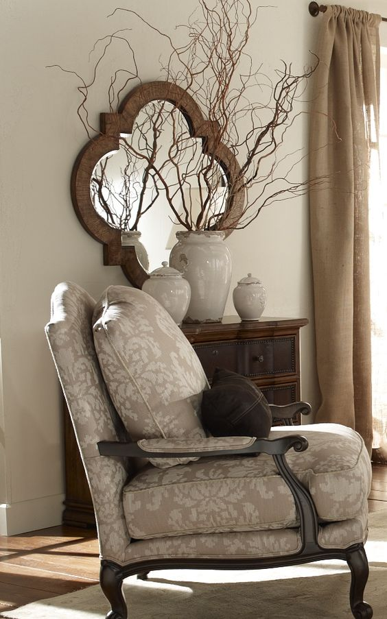 lovely Grey chair and walls with quatrefoil framed mirror.: