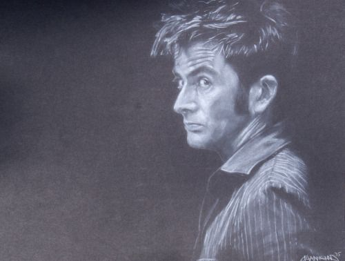 This is a white charcoal drawing of David Tennant on black cardstock. Damn