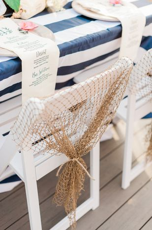 Nautical wedding idea - white chairs decorated with fishing nets {Stephanie Barnes Photography}