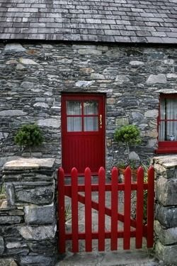 Red door and red picket fence. Stone cottage.