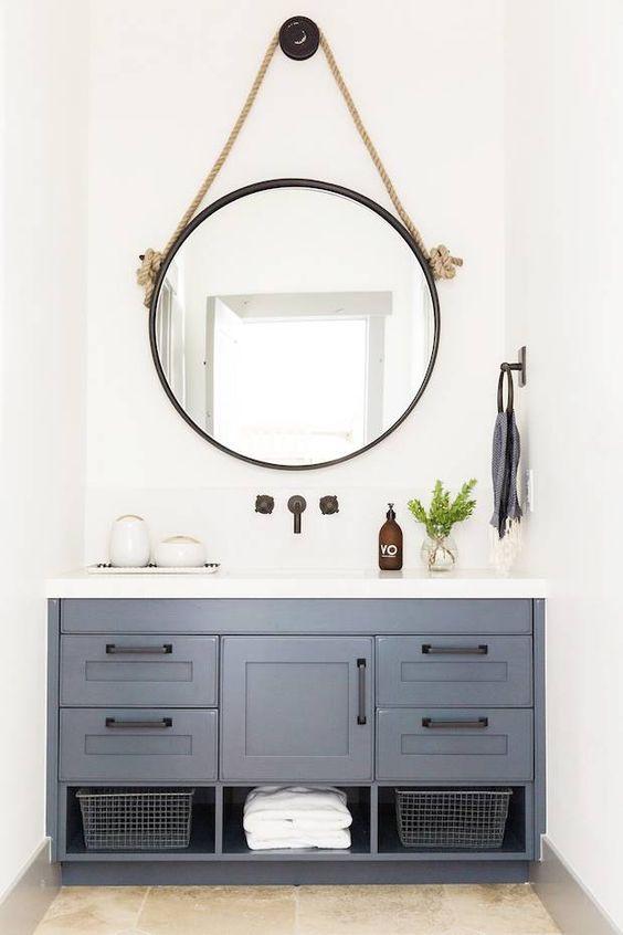 Baño con espejo redondo y mueble de estilo industrial