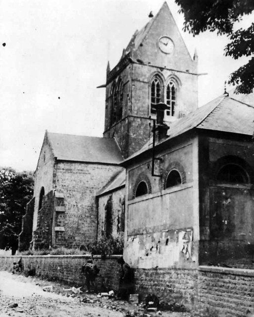 82nd Airborne Troops by church in Sainte-Mère-Église Normandy. The same church where John Steele was caught on the spire (Image).