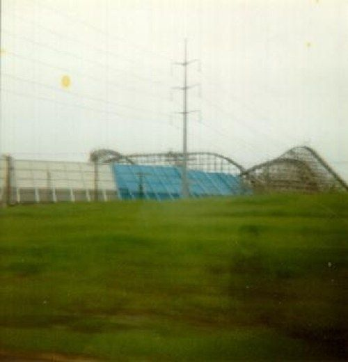 """Taken before smart phones or ghost apps, this photo shows a transparent figure standing near the Six Flags Great America Amusement Park in Arlington, TX. – """"Roller Coaster Boy"""""""