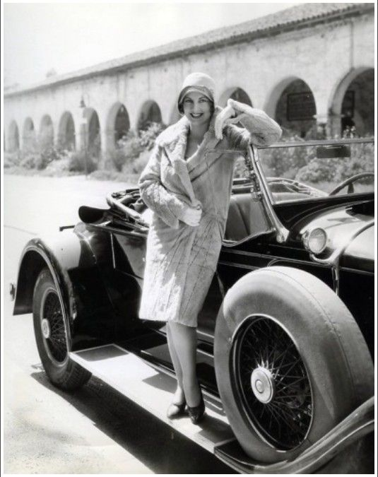 1920s woman in coat with automobile.