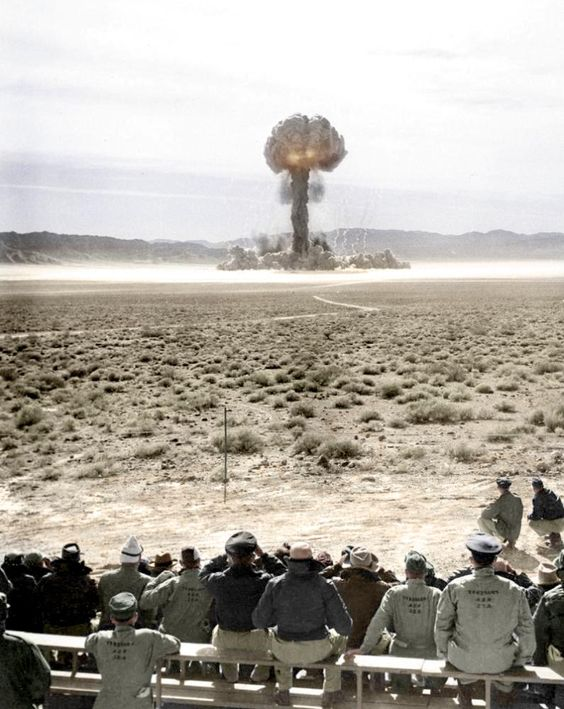 Atomic explosion at Nevada Test Site. (Colorized Photo). This is such a funny and ironic photo. All these people sitting far too close to this explosion, not understanding the consequences and radiation they could get.