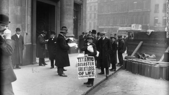 Newspaper boy sells copies of the Evening News on April 16th, 1912 outside of the White Star Line offices in London.