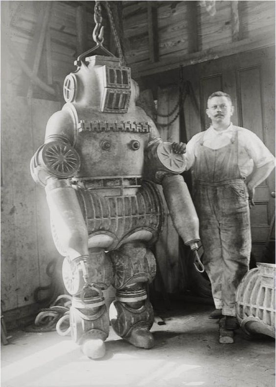 Chester E.                                                Macduffee next to his                                                newly patented, 250 kilo                                                diving suit, 1911:
