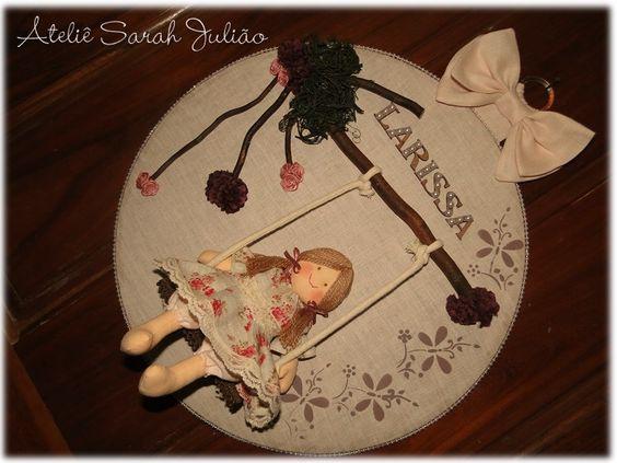 Quadro em madeira MDF com 35 cm de diâmetro forrado em linho com pintura estêncil de borboletas, aplique de galhos secos e flores artificiais e de tecido com uma bonequinha de pano (18 cm) num balanço. Tema: Boneca camponesa.