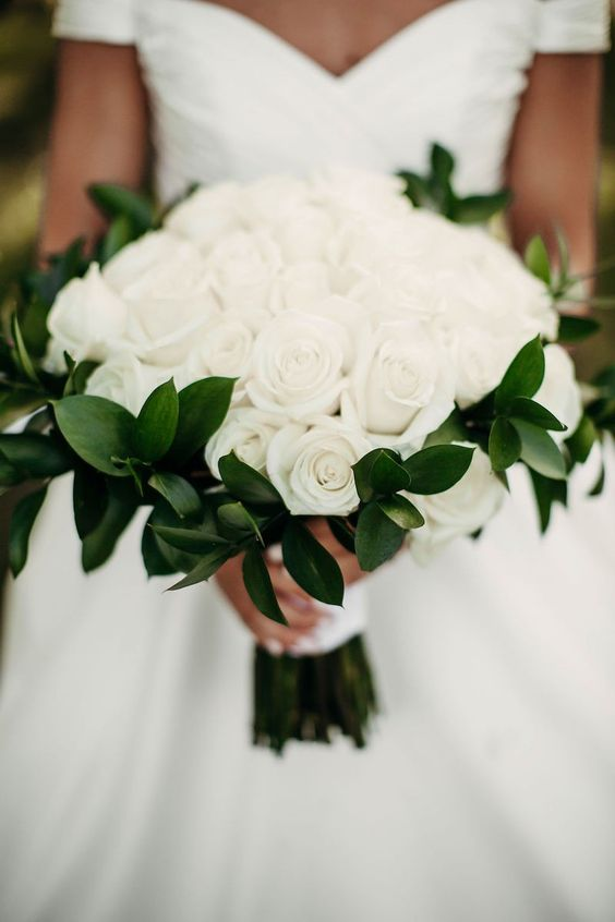 We love the black and white color scheme and the all white roses bouquet for the bride.
