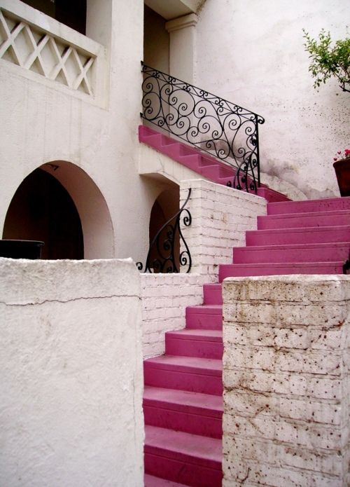 Love the textures with the iron bannister and pink stairs.