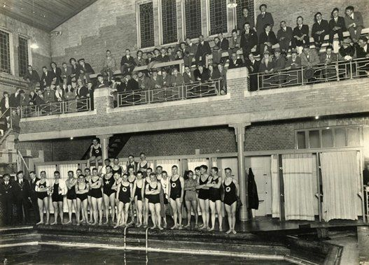 De deelnemers en de toeschouwers van de zwemwedstrijden...