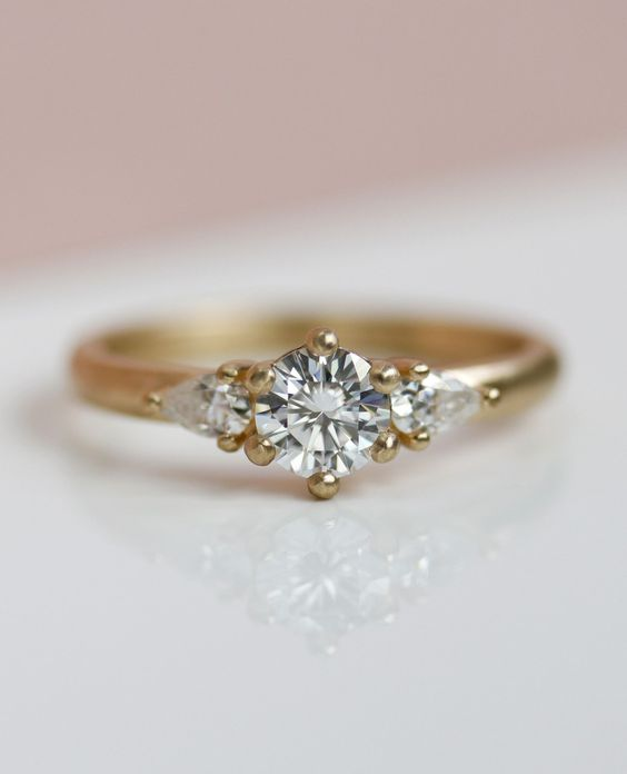 We made this customized version of our Prong-set Three Stone Ring with Pear-Shaped Side Stones, which features a slightly wider band, for a customer in Australia. Pictured here in matte 14k yellow gold with Forever One Moissanite. Handmade to order in our Seattle studio from 100% recycled gold and conflict-free diamonds, fair trade gemstones, and moissanite.