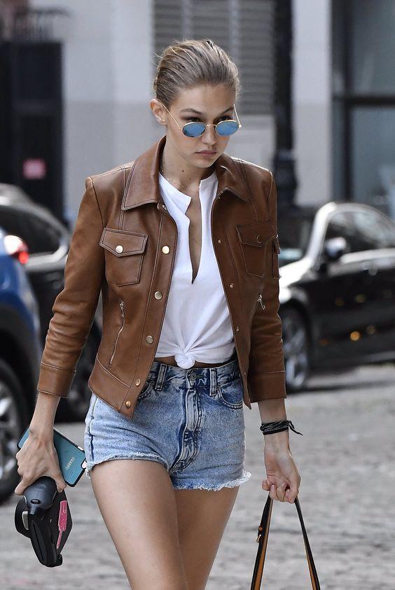 Gigi Hadid, jaqueta de couro marrom, blusa com nozinho na cintura, shortinho jeans desfiado