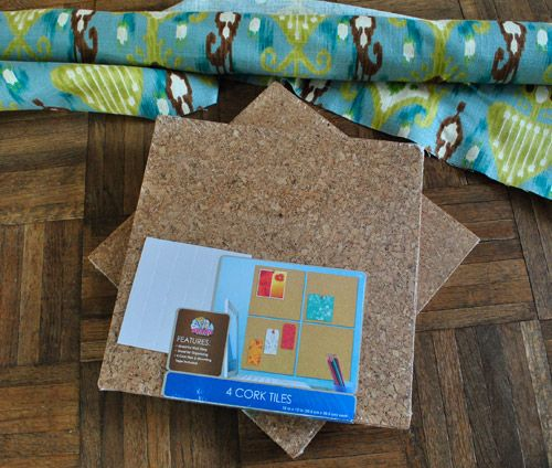 Big corkboard made out of cork tiles and covered with fabric.