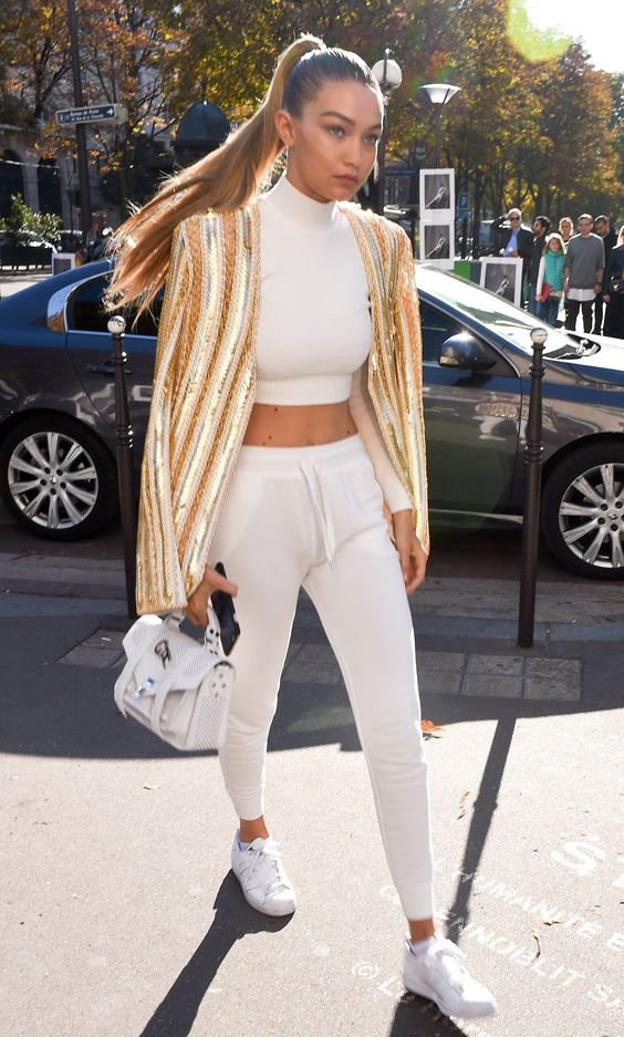 Gigi Hadid in a Jonathan Simkhai cropped turtleneck top, white trousers, white sneakers, and a white Proenza Schouler satchel
