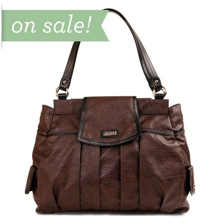 Its deep hot chocolate color gives the Katheryn Shell for Prima Bags a richness that immediately catches your eye. But it's the details of this Shell that make it an absolute must-have for your collection deep classic pleating construction; over-the-top strap closure, convenient snap-close side pockets with chic rivet accents; black faux leather detailing in all the right places. Katheryn is a feast for the eyes that will quickly become your favorite all-occasion take-along accessory.
