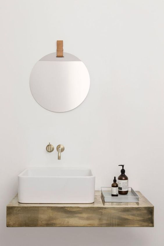 Love this floating wood shelf with basin sink, wall-mounted sink faucet, clear organizing tray and frameless round mirror hanging from a leather strap. Such a modern take on the contemporary neutral bathroom!