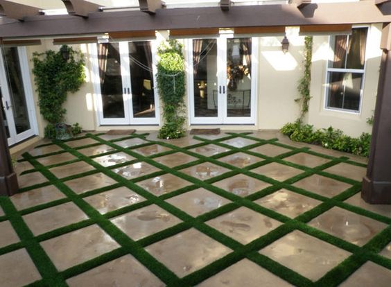 Artificial turf used in grid pattern with limestone pavers for Grid landscape design