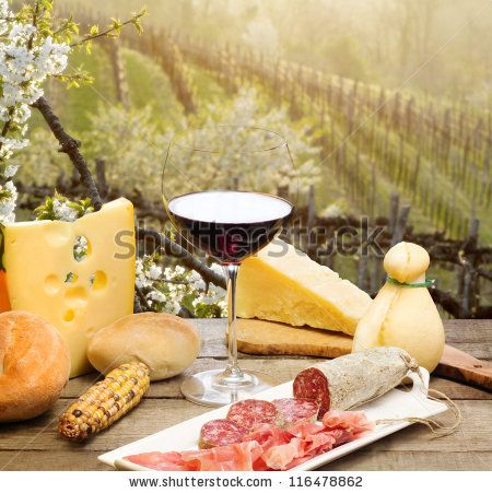red wine glass with cheese and ham against vineyards hill by Donatella ...