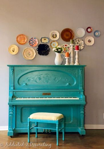 Lindo piano com banquinho turquesa acompanhado de decoração com pratos de parede