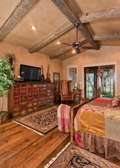 Stained hardwood floors, 200+ year old hand-hewn timbers, and wood-encased doors frame the master bedroom of the ranch foreman's house. Texas Custom Home Builders | Todd Glowka Builder, Inc.