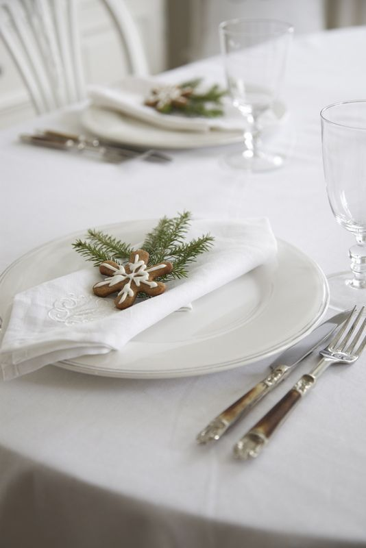 white Christmas table with gingerbread cookies and evergrene sprigs