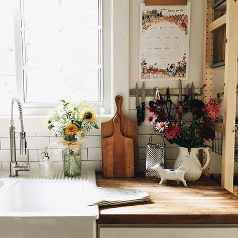 Pia branca grande, torneira articulada e flores naturais na cozinha