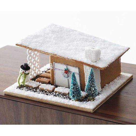 Midcentury Modern graham cracker candy house with snowman and snow.