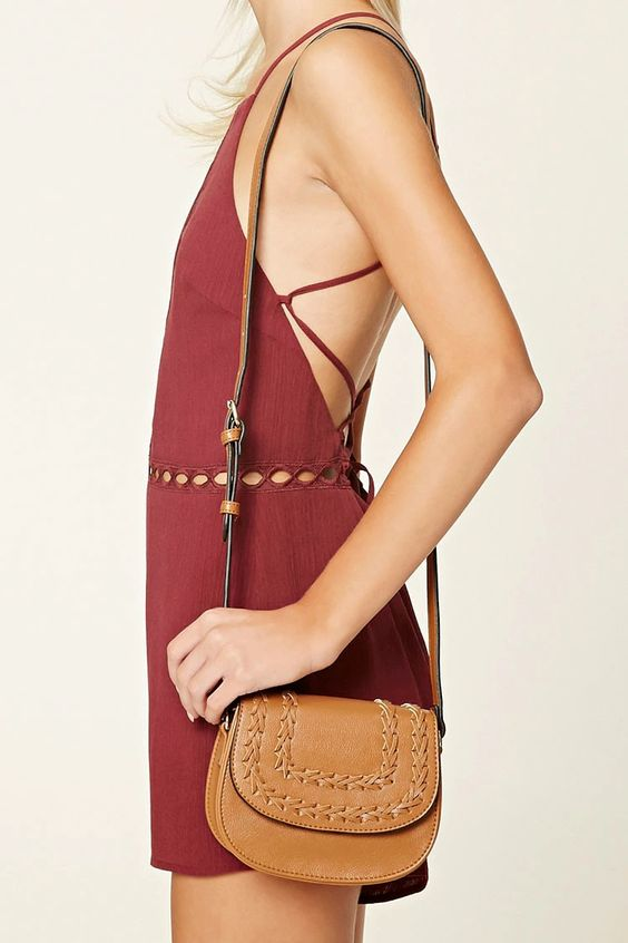 A structured distressed faux leather mini crossbody featuring whipstitched detailing on the flap top with a magnetic snap-button closure, an adjustable shoulder strap, and one interior zip pocket.