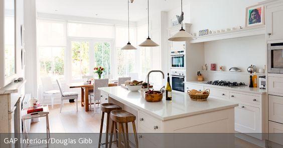 Der lichtdurchflutete Raum wirkt dank der weißen Einbauküche und den Holzelementen noch sommerlicher und natürlicher. Die Barhocker aus Naturholz sind ein Design-Statement und vereinen Natürlichkeit und Moderne.