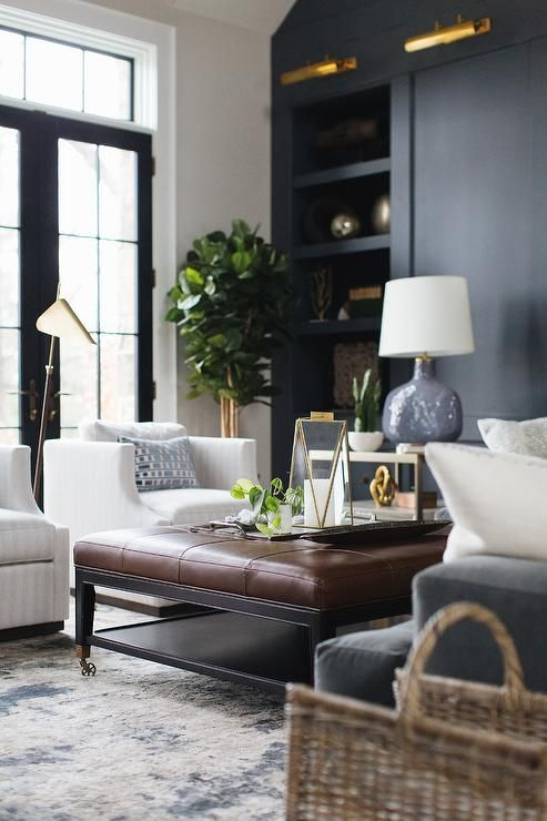 A Brown Leather Tufted Ottoman Sits On A Silver And Blue Rug Between A Gray Velvet Sofa And Side Brown Living Room Living Room Leather Brown Living Room Decor