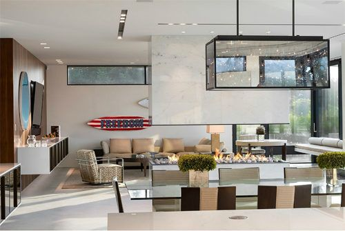 This modern home in the Dunes of Sagaponack has a glass dining table, patterned chairs, track lighting, a glass cube light fixture and open floor plan.
