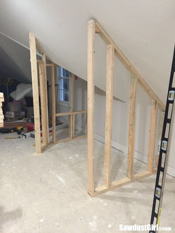 Building a closet around angled ceilings in the loft craft room is a tricky task that required measuring and cutting each stud, one by one.