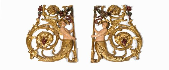A Pair of Carved Giltwood Scrolls with Putti, Italian, 17th C. - Architectural decorations, carved as a bold large scroll set with a polychrome painted putti - Dim: Each: 150 x 117 x 16 cm.
