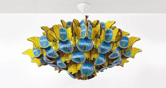 """Die Anleitung zu diesem tollen Kronleuchter von Anneke, Künstlerin und Designerin aus den Niederlanden, kann man hier für 5 Euro erstehen.    Anneke schreibt: """"Der Chiquita Leuchter ist handgemacht aus 29 Bananenkisten und Heftklammern. Er hat einen Durchmesser von 110 cm und ist 50cm hoch, mit einer Lichtquelle. Der Leuchter erzeugt Stimmungslicht."""