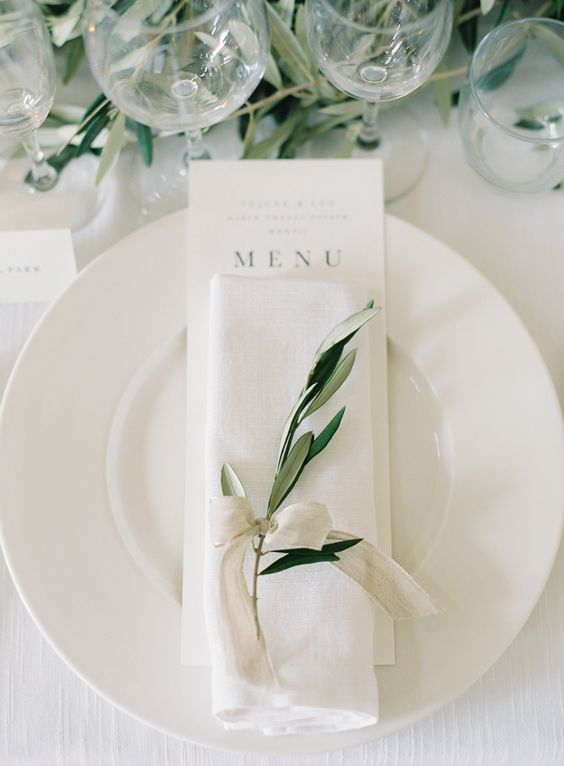 While on white accented by the prettiest touch of greenery makes this place setting special!