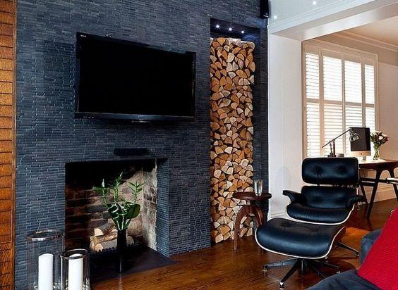 rangement bois de chauffage à côté de la cheminée habillée de tuiles grises