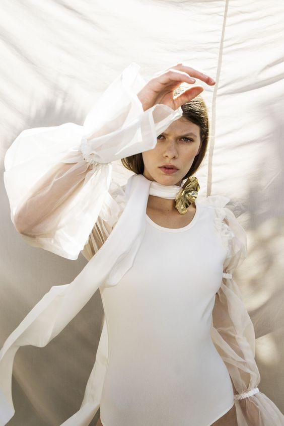 A model wearing a white bodysuit and sheer shirt from the Maggie Marilyn pre-fall 2019 collection.