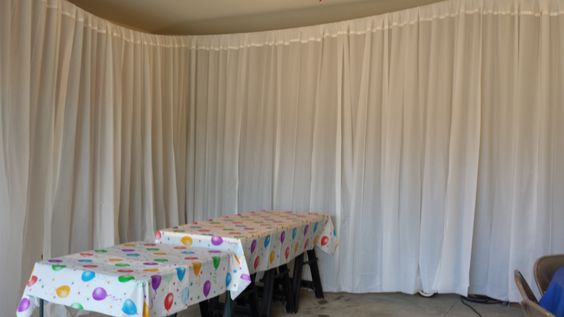 using plastic table cloths from the Dollar Store, and a roll of white duct tape.  Folded over the top of the table cloths and carefully taped with 1/2 wide white duct tape.  Then hung with clothes line.  Cover up ugly wall space!