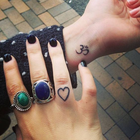 Small wrist tattoo of an Om and a finger tattoo of a small heart on Steph.: