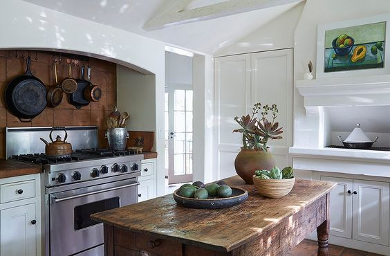 """This kitchen is not just for show. """"That stove is constantly in use,"""" says Kendall. """"And our table is always full of fresh produce from our garden."""" A silver ice bucket corrals wooden spoons beneath iron and copper pots. A painting by Kendall's sister, Cayetana hangs above a traditional tagine.:"""