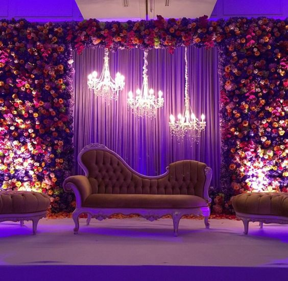 Beautiful Bride & Groom Sitting with floral backdrop and chandeliers | Function Mania #Trending: How to use hues of Ultraviolet for a chic wedding decor!