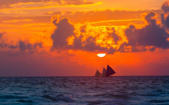 Sailboats at sunset seen from the shores of Boracay Island Philippines.