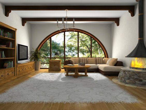Maskulin Wohnzimmer mit großen halb Kreis Fenster, große Sektionaltore, graue Wolldecke auf hellen Holzfußboden. Offenen Gaskamin und montierte Flachbildfernseher schmücken die Wände.