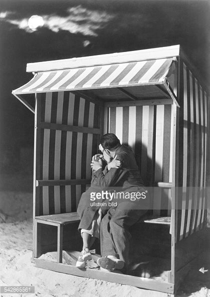 Love Lovers kissing each other under the full moon in a roofed wicker beach chair 1937 Published by 'Koralle' 29/1937 Vintage property of ullstein...